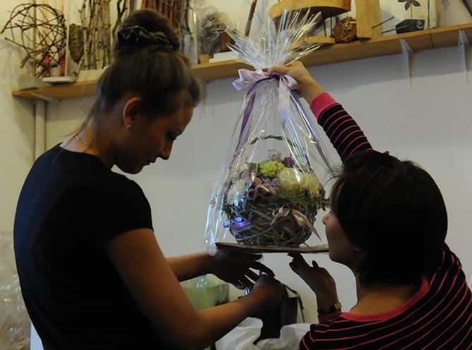 Студенты учатся упаковывать корзину из цветов